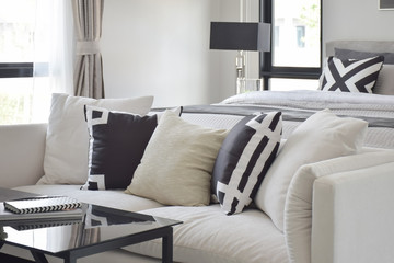 Black and white graphic printed pillow on off white sofa next to bed