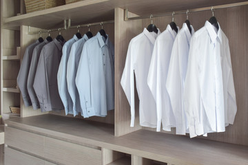 Classic color shirts hanging in warm wooden wardrobe