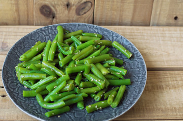 Plate with cooked green beans with sesame seeds on wooden background