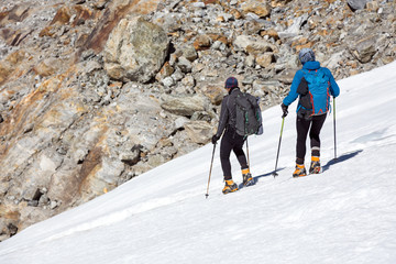 Mountain Climbers Man and Woman walking on steep Ice Slope
