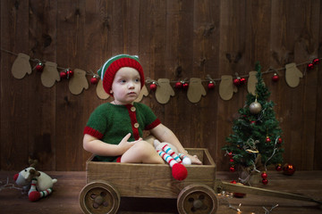 little boy dressed as a Christmas elf sits in a wooden cart. Christmas concept.