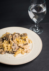 Pasta with grilled mushrooms and chicken on the dark wooden background