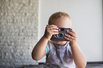 small child holding a camera. Boy photographs