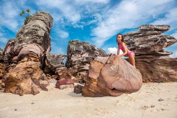 Woman in pink bikini on a rocky beach