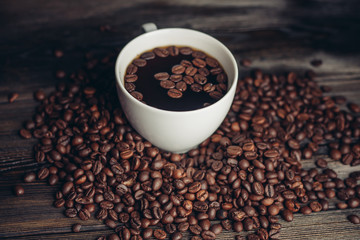 Coffee beans on the table and drink in the cup