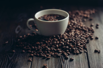 cup with a drink and coffee beans around