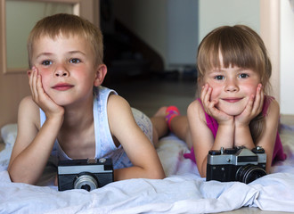 Children boy and girl brother and sister playing with cameras. Family relations concept.