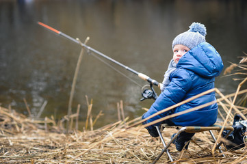 Little boy fishing on the river bank