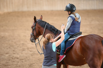 Girl in helmet Learning Horseback Riding. Instructor teaches teen Equestrian.