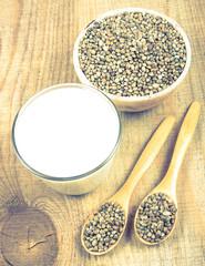 Hemp milk, seeds on wooden background . Close Up .