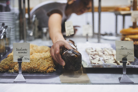 Hand of a woman working in a bakery and arranging muffins.