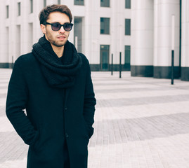 Fashion. Style. A young man in a fashionable black coat and sunglasses and snood posing near the business center. Close up. Outdoor.