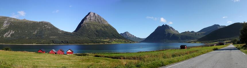 Panorama: Straße entlang des Fjord Aldersund und Blick auf die Insel Aldra mit markantem Berg in Nordland, Norwegen