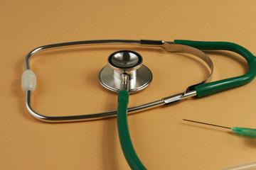 Stethoscope and syringe on orange background.