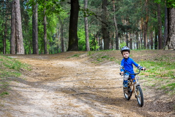 Happy cute blond kid boy having fun his first bike on sunny summer day, outdoors.  child making sports. Active leisure for children.  wear safety helmet.  is smiling and cicling