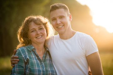 Portrait of mother and son, outdoors. Nature background.