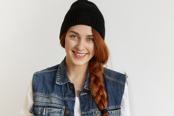 People and lifestyle concept. Portrait of beautiful cheerful redhead girl wearing stylish black winter hat and sleeveless denim jacket smiling happily while posing isolated at white studio wall