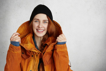 Style, fashion, advertisement and clothing design concept. Indoor shot of beautiful redhead Caucasian girl in black hat, smiling happily, adjusting hood of her trendy red winter coat with both hands