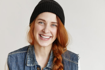 Portrait of beautiful redhead young Caucasian woman wearing stylish black hat and denim sleeveless jacket looking at camera with happy and cheerful smile, standing against white studio wall background