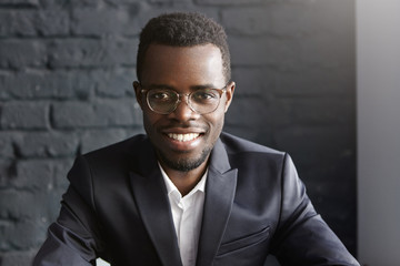 Portrait of confident and successful young African-American businessman wearing stylish glasses and elegant dark formal suit smiling happily, rejoicing at profitable deal he has just concluded