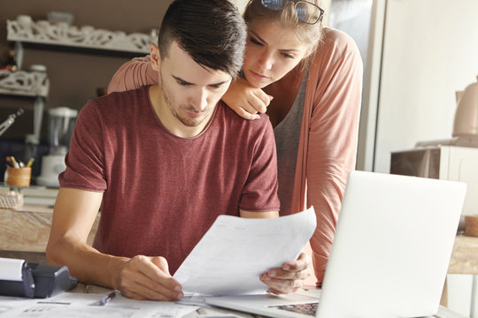 Young American couple calculating bills online using laptop computer at home. Concentrated husband and his wife studying piece of paper while working through domestic finances in kitchen together