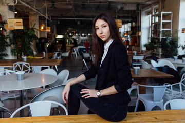 Portrait of a young cute brunette girl business in the interior hipster cafes. Long hair.