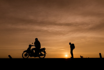 Silhouette of  backpacker  who were traveling,a motorcycle ride through.The background image is a sunset in Thailand.