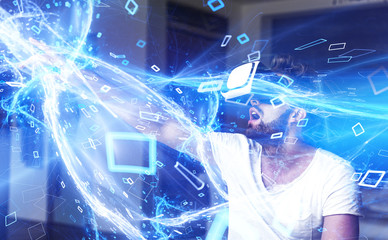 Young man with VR glasses playing virtual reality, high energy lightning media stream
