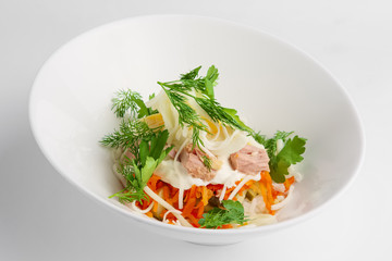 Plate with tuna salad with eggs, carrot, onion and mayonnaise on white background