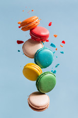 Different types of macaroons in motion falling on light blue background.