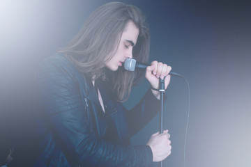 rocker with long hair singing in microphone