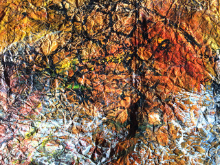 Painted creased paper in a mix of autumnal colors including  black, brown, orange, yellow, green and white creating a textured abstract background with space for text.