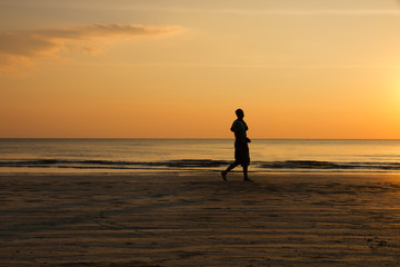silhouette of a man jogging on the beach at sunset, healthy lifestyle
