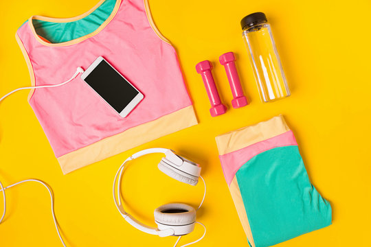 Sport equipment and clothes with mobile phone on yellow background. Top view