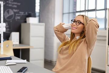 junge frau im büro lehnt sich zufrieden zurück