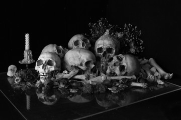 Pile of skulls with bone and pile of withered dry flowers with candle light on plastic plate