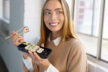 lächelnde frau mit sushi