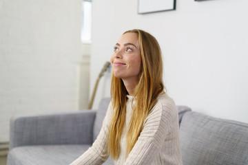 frau sitzt entspannt auf dem sofa und schaut lächelnd nach oben