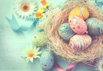 Fotoväggar - Easter colorful eggs with decorations over blue wooden background