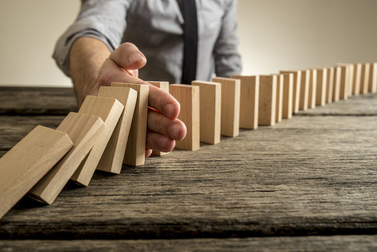 Man stopping domino effect on wooden table