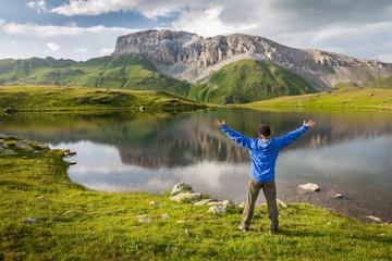 Man enjoying beautiful summer mountain landscape during his hiking trip