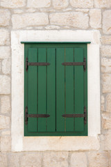 Closed green shuttered weathered wooden window
