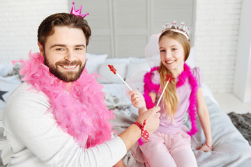 Smiling positive father giving lollipop to his daughter
