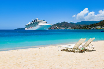 Cruise ship in Caribbean Sea with beach chairs on white sandy beach.