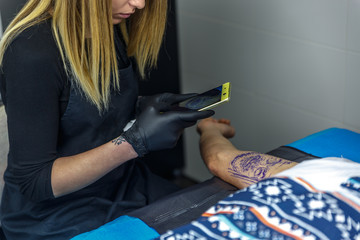 A tattoo artist girl photographing the tattoo she is doing to her client