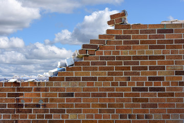 crumbling brick wall with fluffy cloud sky background