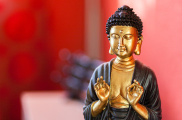 Buddha sculpture in front of a red background