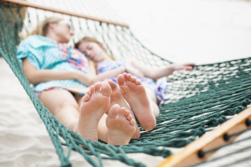 Barefoot and Relaxed family napping in a hammock together outdoors on a sunny day. Selective focus on the feet