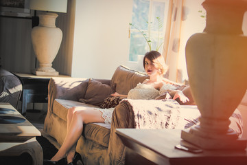 beautiful young woman sitting on the sofa in the luxury room