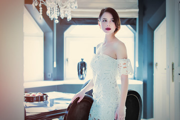 beautiful young woman standing near the table in the light luxury room and touching one of the chairs